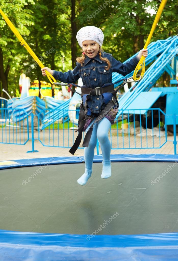 happy little girl jumping on trampoline