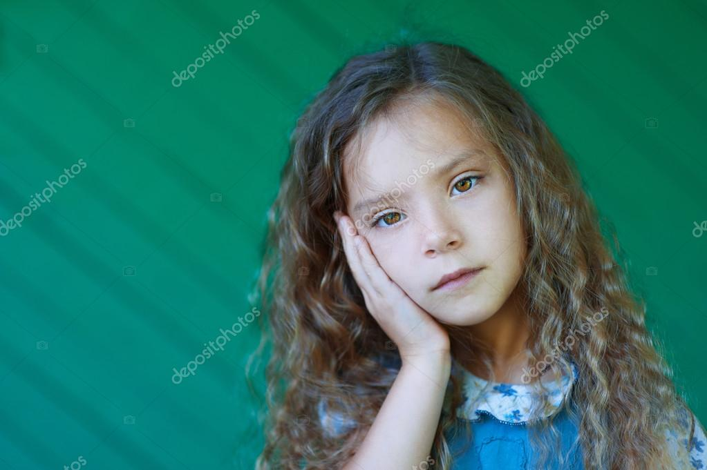 beautiful sad little girl with curly hair close up