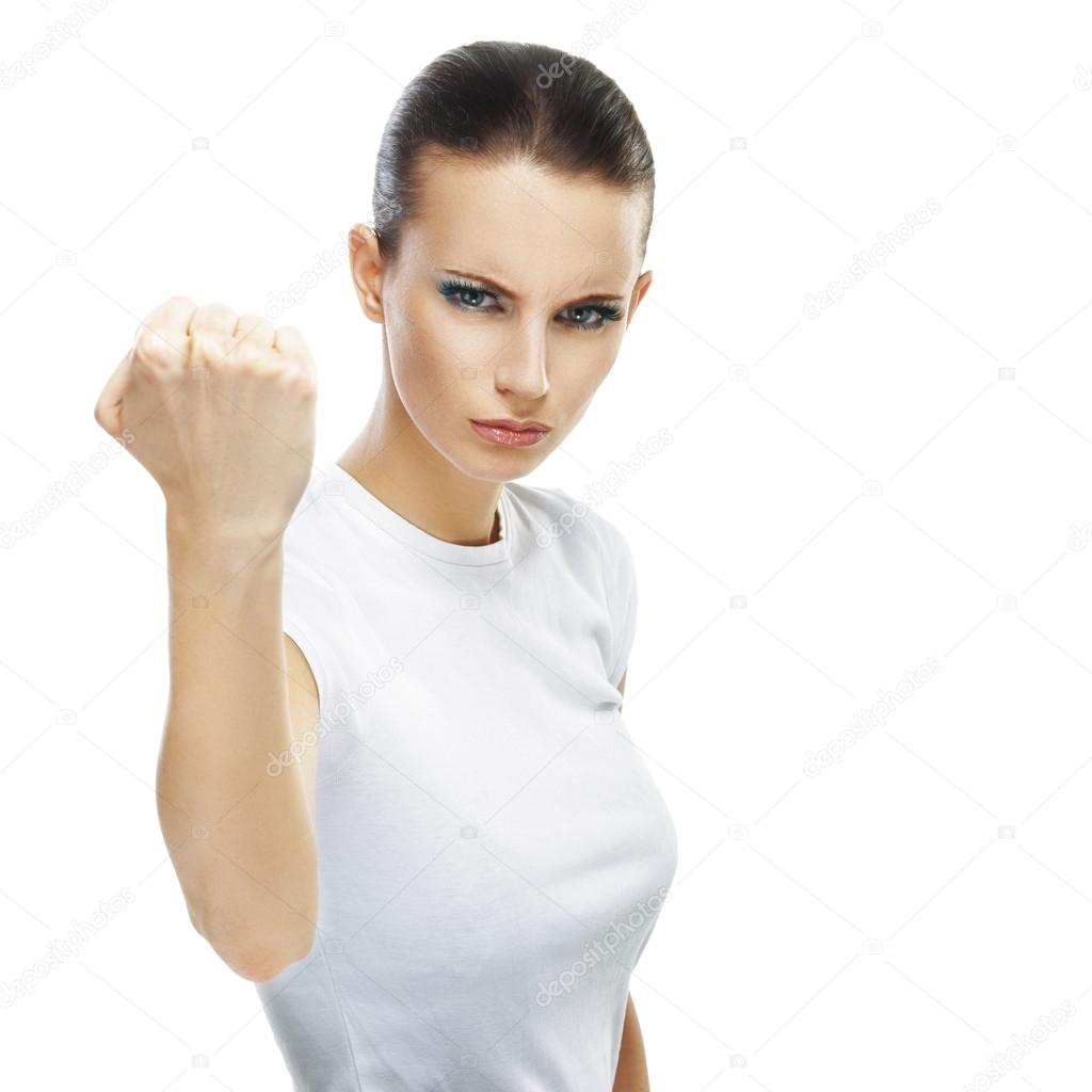 Beautiful sad young woman close-up threatens fist into camera, isolated on white background.