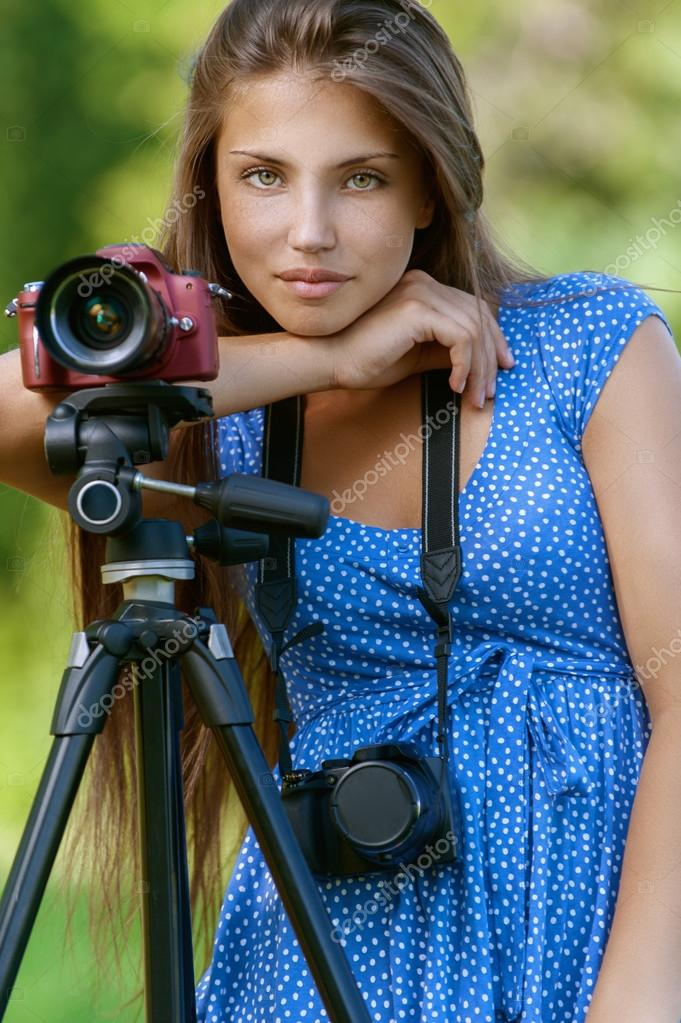calm young woman with camera on tripod