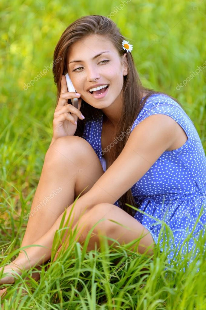 woman sitting on grass and talking on phone