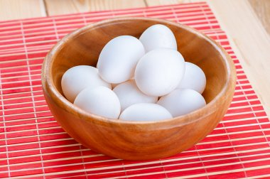 White chicken eggs in wooden bowl on red napkin. stock vector