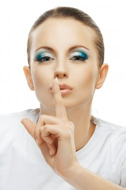dark-haired woman raised index finger to lips