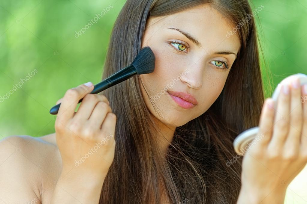 young woman is brushed powder on face