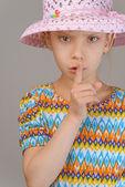 Fotografia bambina mette il dito indice per labbra