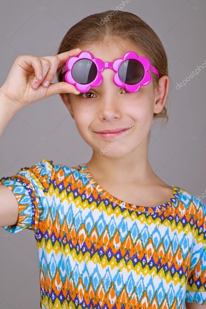 12e4ae8d76 Belle petite fille gaie avec lunettes de soleil sur fond gris — Image de  BestPhotoStudio