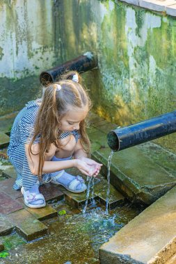 Little girl drinks water from source