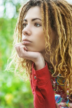pensive woman with dreadlocks closeup