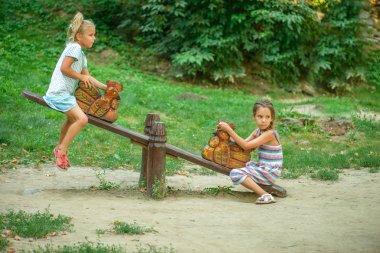 Two sisters ride on swings