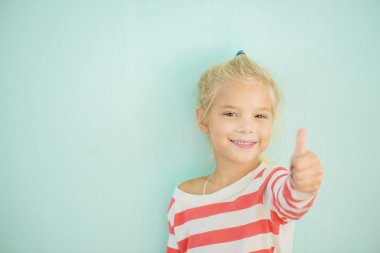 Little cheerful girl lifts thumb upwards, on green background. stock vector