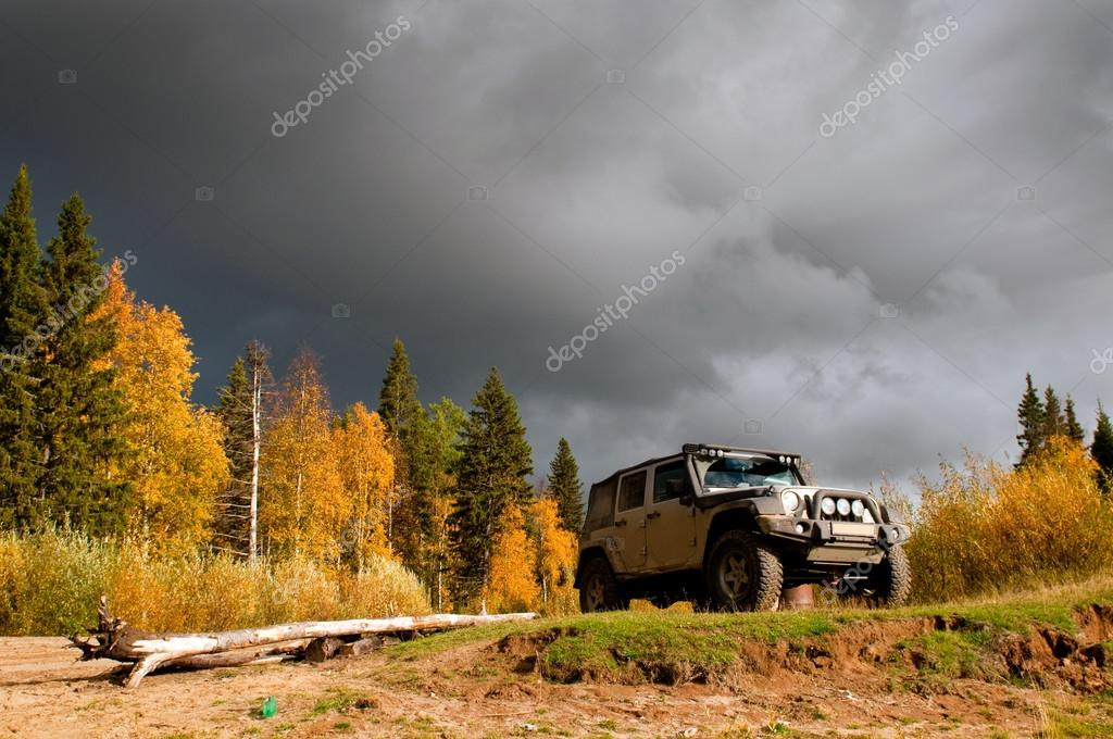 SUV on wild mountain road in deep taiga forest