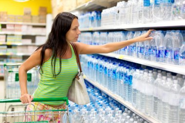 A woman buys a bottle of water in the store