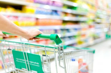 Cropped image of female shopper with cart at supermarket
