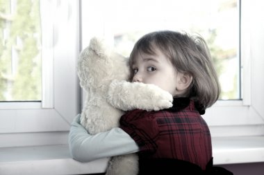 Frightened little girl hugging teddy bear