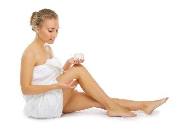Young healthy girl applying body cream isolated