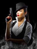 Porträt einer Frau im männlichen Stil mit Pistole und Rauch