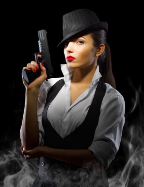 Portrait of woman in manly style with gun and smoke