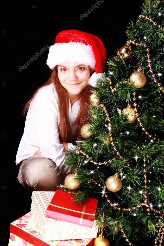 Girl with christmas tree and presents over dark