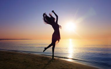 Silhouette of the woman dancing at the beach during beautiful sunset. Natural light and darkness. Artistic vivid colors added stock vector