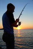rybář ryby na západ slunce