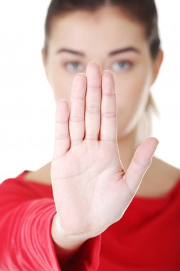 Confident woman making stop gesture sing
