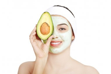 Young woman with a smile holding with avocado