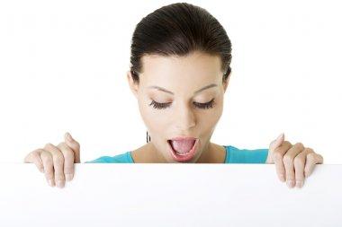 Shocked woman holding blank board