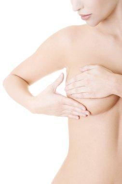 Caucasian adult woman examining her breast