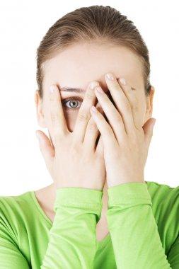 Shy or scared teenage girl peeking through covered face