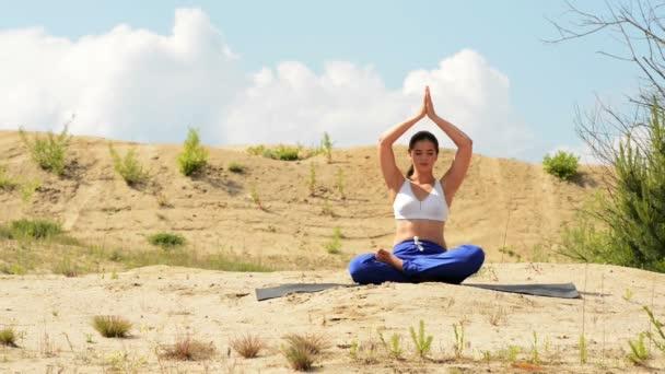Attraktive Frau praktiziert Yoga in der Natur.