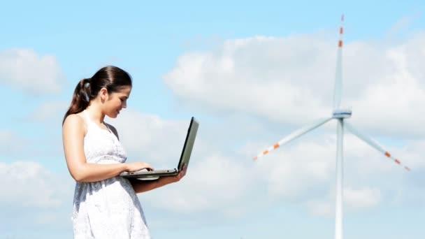 ragazza adolescente con computer portatile accanto a turbina eolica
