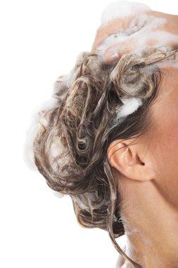 Close up on female's head with shampoo.