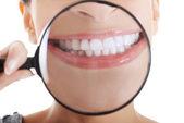 Schöne Frau mit Lupe zeigt ihre perfekte weiße Zähne