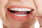 junge schöne Frau mit Zahnseide