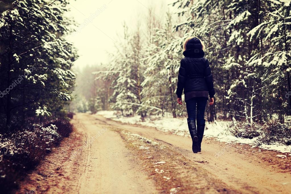 Woman is walking through forest in wintertime