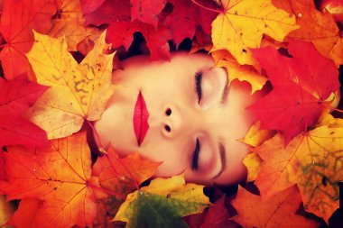 Woman face in autumn leafs