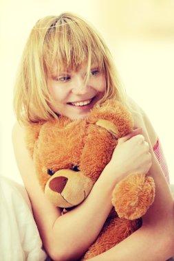 Kid embraces teddy bear