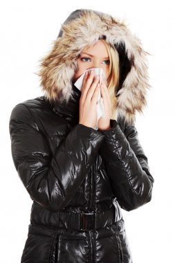 Woman sneezes during cold day