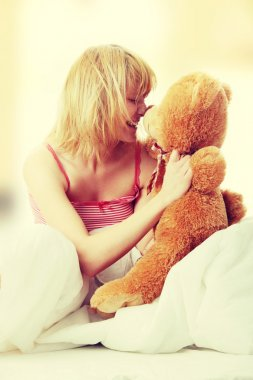 Woman in bed embraces teddy bear