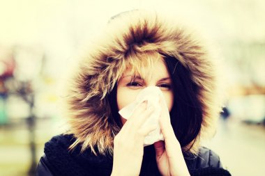 Young woman sneezes during cold day.