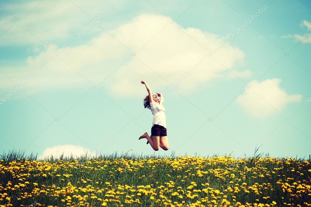 Woman jumping on blossom meadow.