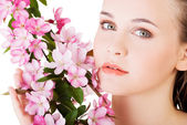 Woman with healthy clean skin and pink flowers