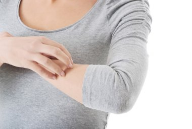 Young woman is scratching herself on arm.