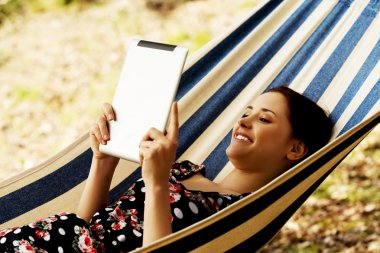 Woman Relaxing In Hammock With  E-Book