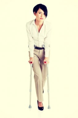 Young businesswoman with crutches