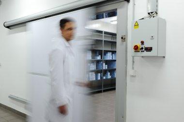 Young worker opening door of industrial refrigerator, blurred motion