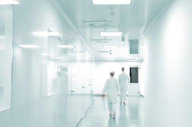 Working with white uniforms walking in modern factory environment