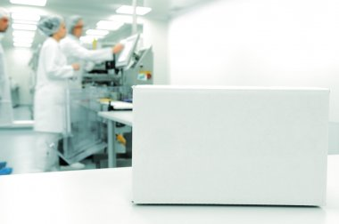 White box at automated production line at modern factory, working in background