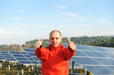 Male worker at solar panel field show sign ok