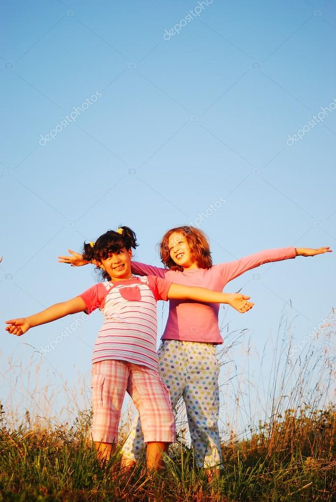 Two happy female children standing outdoor with hands up